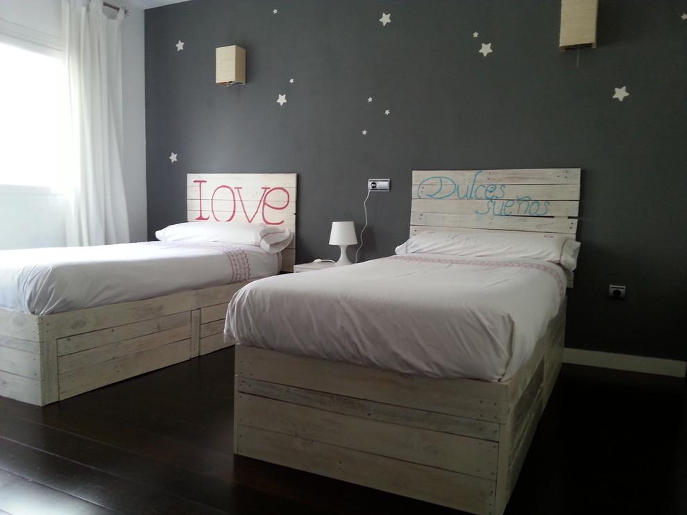 Habitación infantil con dos camas individuales hechas con palets